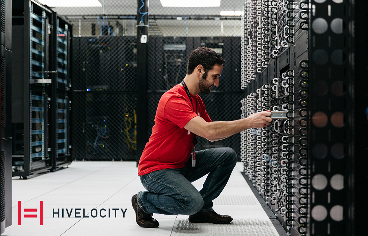 Man kneeling in front of server cabinet with Hivelocity logo by his foot