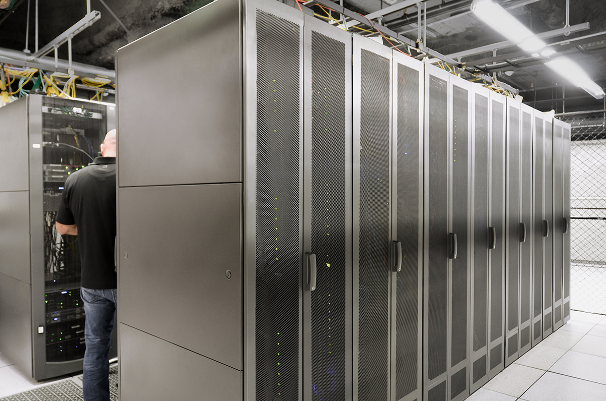 A Hivelocity employee standing between rows of filled server cabinets
