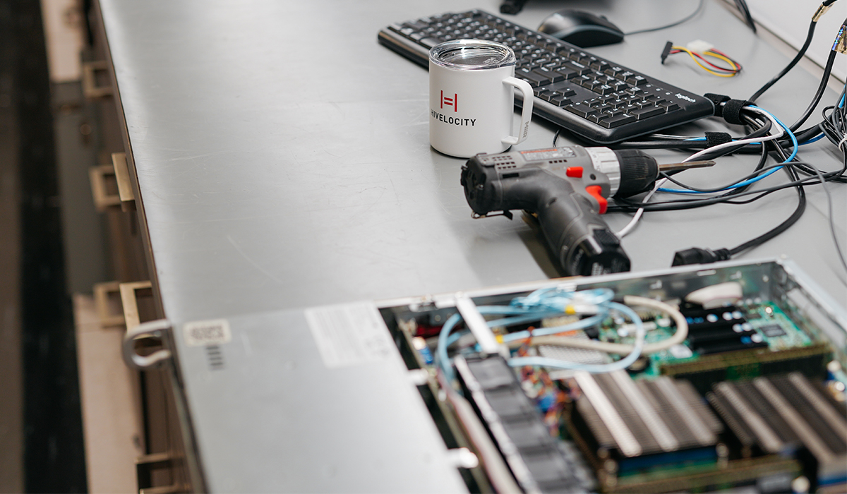 A opened server sitting on a table next to a power drill and coffee mug with the Hivelocity logo